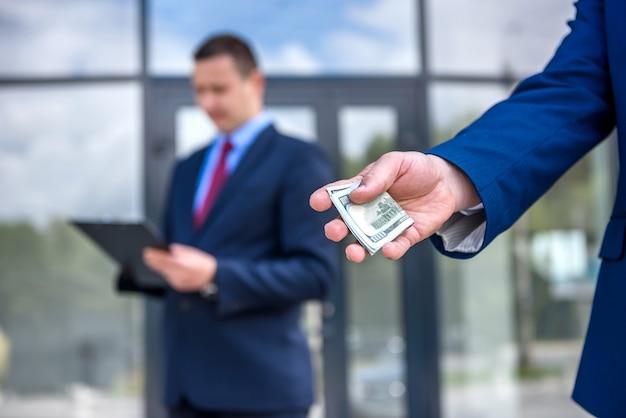 Mains mâles avec des billets en dollars à l'extérieur se bouchent