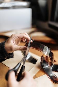 Mains mâles coupant un film vintage 35 mm