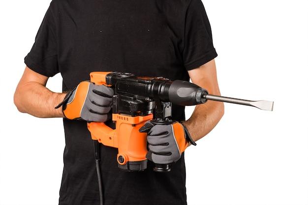Mains mâles dans des gants de protection tenant un nouveau grand perforateur électrique avec une longue perceuse