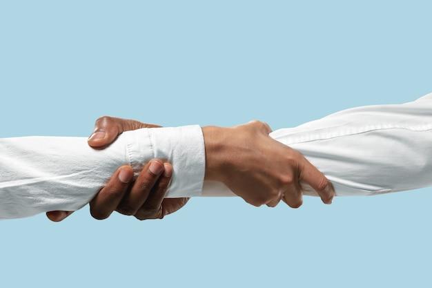 Mains mâles démontrant un geste de tenue et fort isolé sur fond bleu studio.