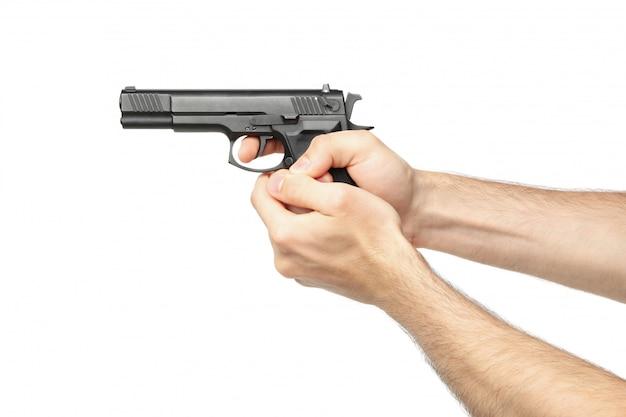 Mains mâles détiennent un pistolet noir, isolé sur blanc