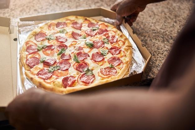 Mains mâles emballant une délicieuse pizza au pepperoni dans une boîte de livraison