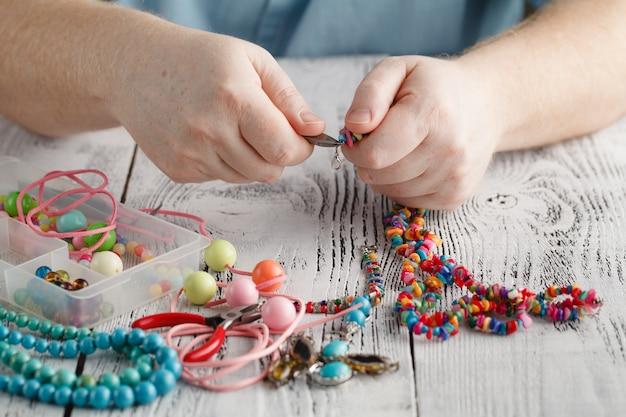 Mains mâles faisant un collier avec des perles en bois
