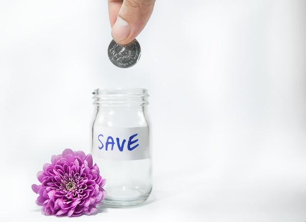 Mains mâles gouttes coin thai argent dans un bocal en verre et fleur pourpre.