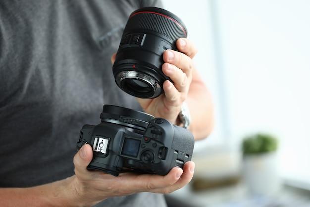 Mains mâles mettant sur appareil photo numérique moderne objectif professionnel gros plan