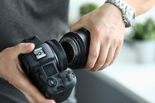 Mains mâles mettant sur l'objectif professionnel de l'appareil photo numérique moderne