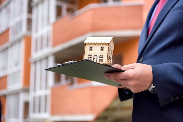 Mains mâles avec presse-papiers et modèle de maison en bois se bouchent
