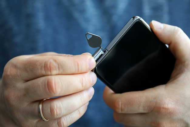 Mains mâles se fente pour carte sim de son smartphone
