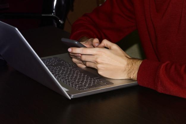Mains mâles avec smartphone en eux. ordinateur portable sur la table. employé de bureau.