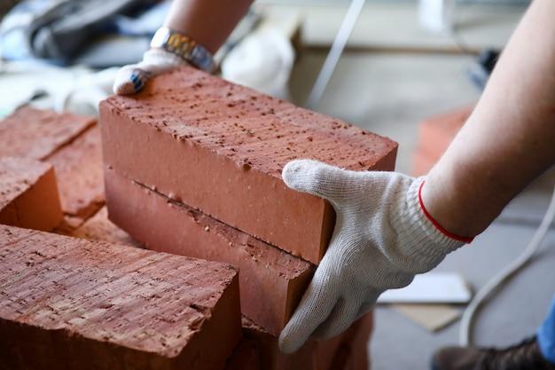 Mains mâles soulevant plusieurs briques rouges au gros plan du chantier