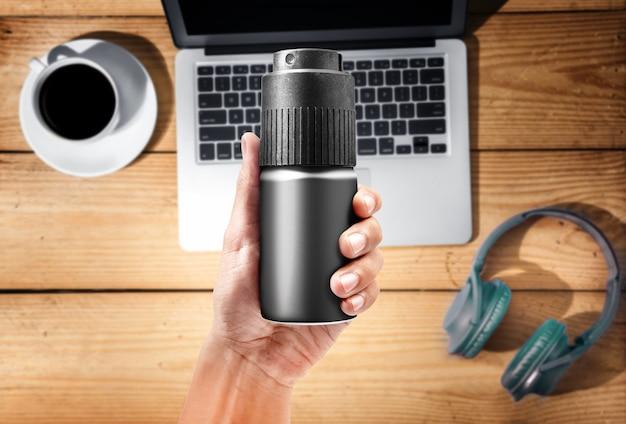 Mains mâles avec spray corporel, ordinateur portable, casque et tasse de café sur le fond en bois