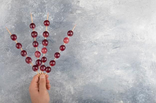 Mains mâles tenant des bâtons de raisins rouges sur fond de marbre.
