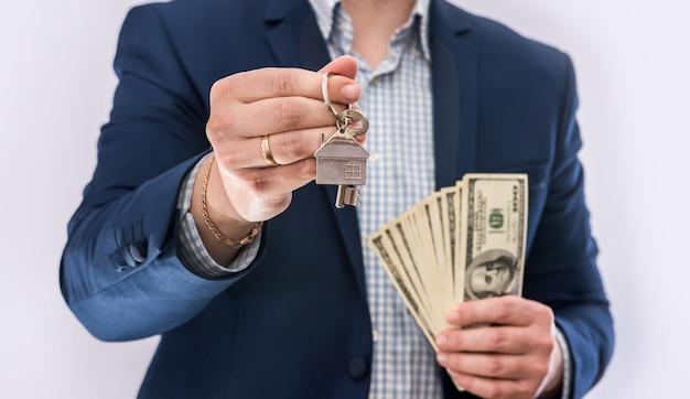 Mains mâles tenant des billets en dollars américains et une clé de maison isolée. concept achat ou prêt immobilier