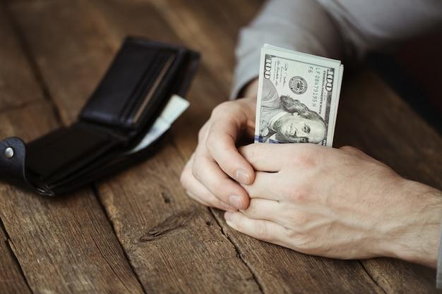 Mains mâles tenant des billets en dollars sur la vieille table en bois