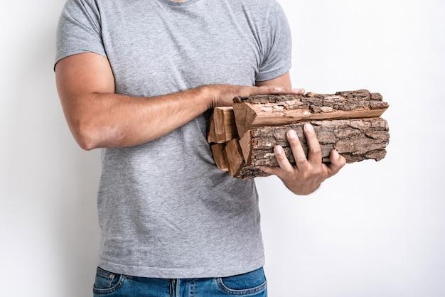 Mains mâles tenant un bois de chauffage