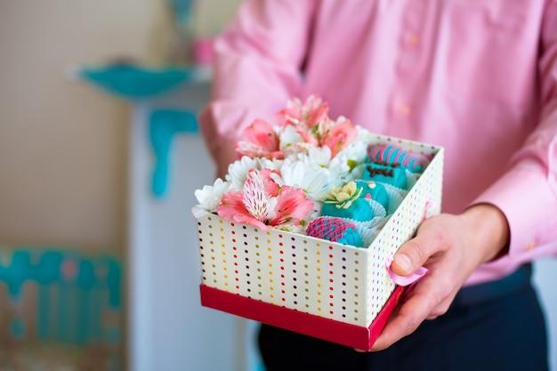 Mains mâles tenant une boîte-cadeau remplie de fleurs et de bonbons aux fruits