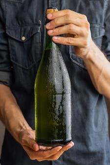 Mains mâles tenant une bouteille bouchée de cidre premium. belle bouteille glacée de vin de pomme dans les mains de l'homme