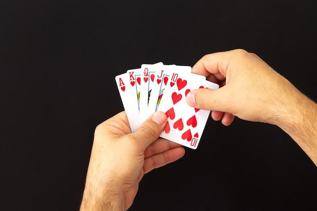Mains mâles tenant combinaison de cartes de poker royal flush sur fond sombre. concept de casino, chance et fortune