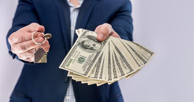Mains mâles tenant des factures en dollars américains et clé de la maison isolée. achat concept ou prêt immobilier