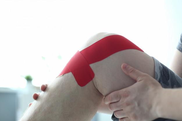 Mains mâles tenant une jambe blessée sur blanc