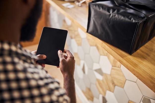 Mains mâles tenant un ordinateur portable électronique tandis que l'homme se tient près du comptoir avec un sac de livraison de nourriture