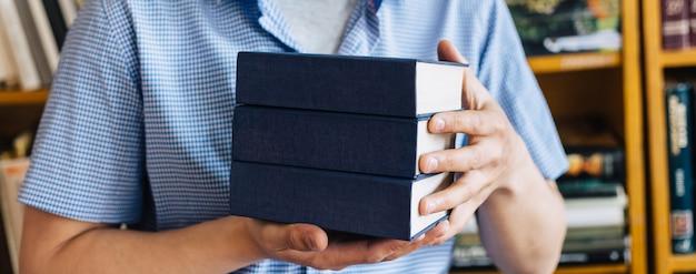 Mains mâles tenant une pile de livres.