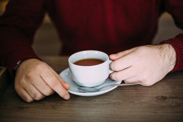 Mains mâles tenant une tasse de thé dans un café