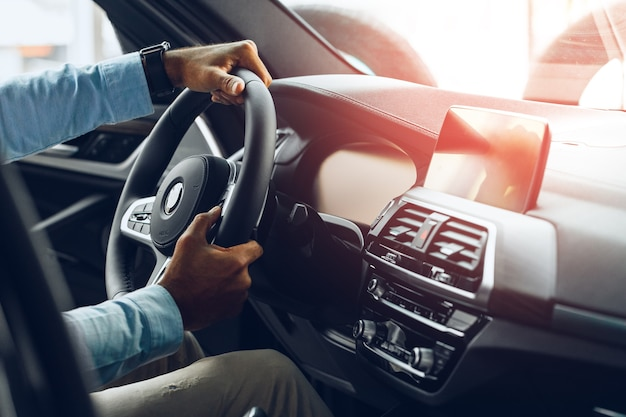 Mains mâles tenant le volant d'une voiture