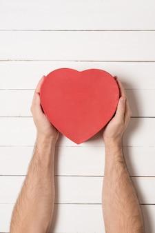 Mains mâles tiennent une boîte en forme de coeur rouge sur une table en bois blanche