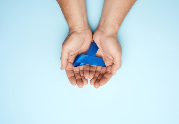 Mains mâles tient un ruban bleu foncé, concept de recherche en temps opportun et de prévention des maladies cancéreuses du côlon, syndrome de fatigue chronique, sclérose tubéreuse, vue de dessus