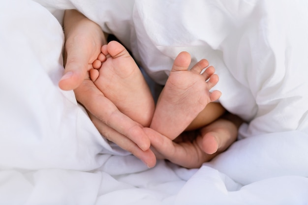 Mains d'une maman caucasienne tenant les petites jambes de son bébé bébé africain noir.