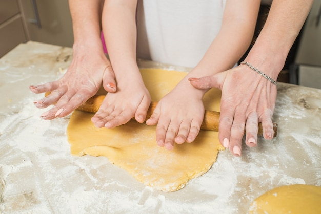 Mains de maman et fils qui roulent la pâte dans la cuisine. cuisiner à la maison
