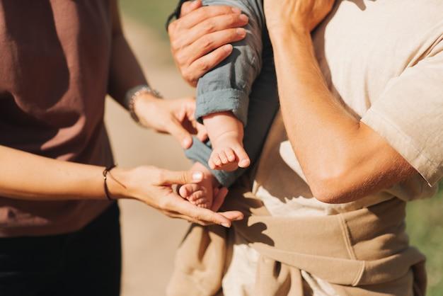Les mains de maman et papa tiennent les petits pieds d'un bébé