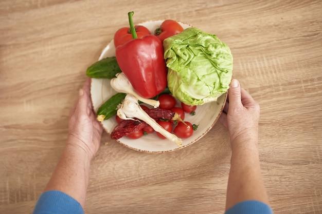 Mains de mamie offrent des légumes maison frais.