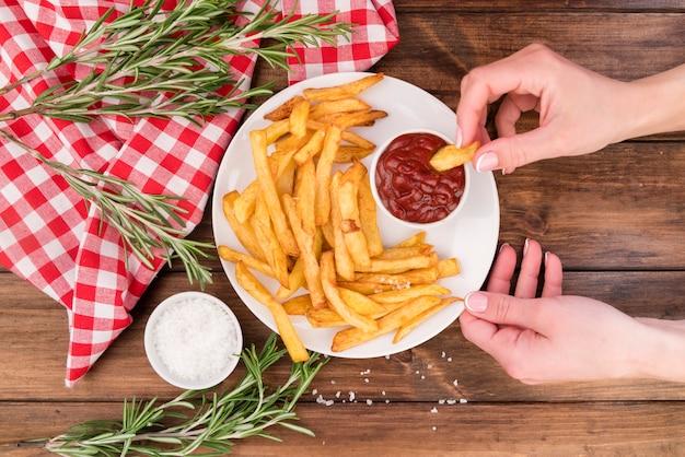 Mains mangeant de délicieuses frites