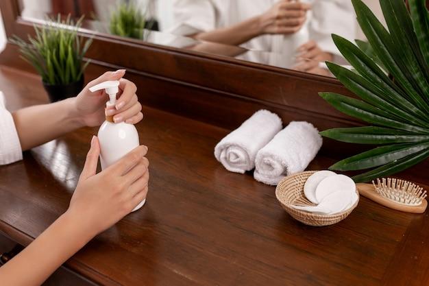 Les mains d'un mannequin tenant une bouteille blanche posée sur une table brune sur laquelle sont posés des produits de soin: peigne, serviettes, cotons-tiges et un pot de fleurs. les produits de soins personnels.
