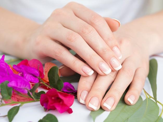 Mains manucurées avec des fleurs colorées