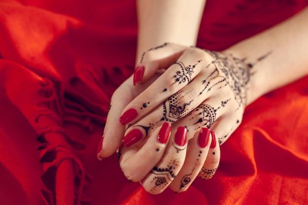 Mains manucurées rouges avec mehndi