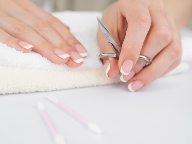 Mains manucurées tenant des ciseaux à ongles
