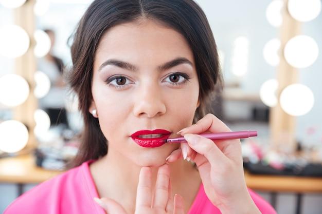 Mains d'une maquilleuse avec un pinceau à lèvres appliquant du rouge à lèvres rouge aux lèvres d'une jeune femme séduisante dans un salon de beauté