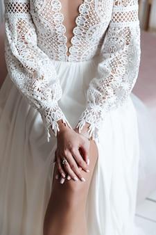 Les mains de la mariée avec une bague de mariage dans une robe de mariée avec de la dentelle boho. séance photo de mariage.