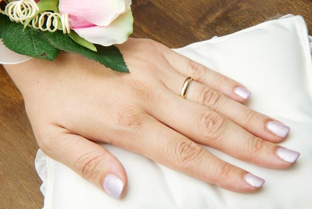 Mains de mariée avec bague de mariage et roses sur oreiller blanc
