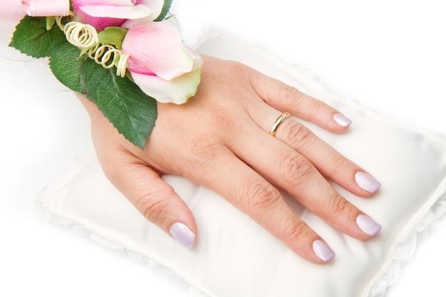 Mains de mariée avec bague de mariage et roses