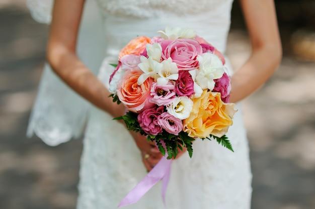 Mains de la mariée beau bouquet de mariée