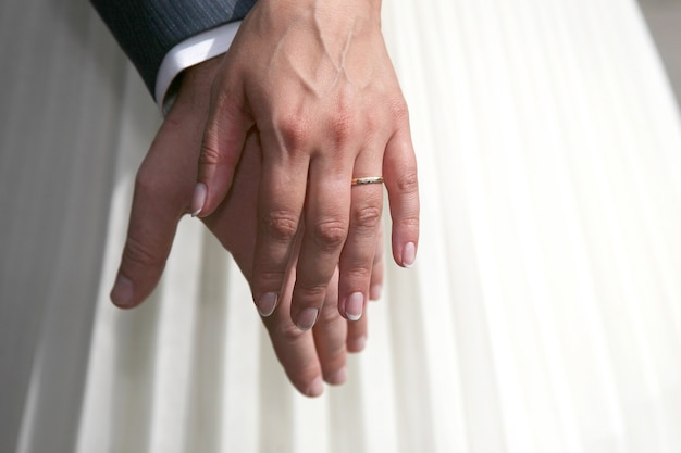 Mains de la mariée et du marié ensemble. relations amoureuses et familiales