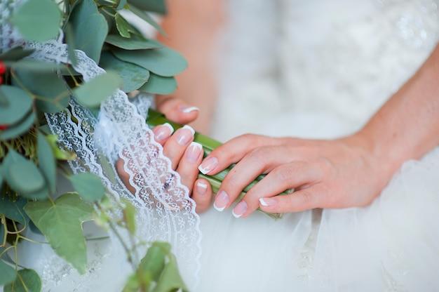 Les mains d'une mariée, juste marié, un bouquet de mariée est à côté