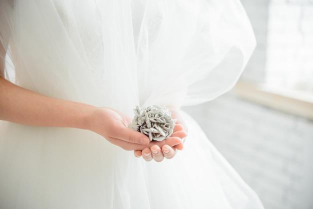 Mains de mariée avec manucure en gants de dentelle blanche