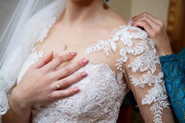 Les mains de la mariée se sont croisées sur une robe de mariée blanche