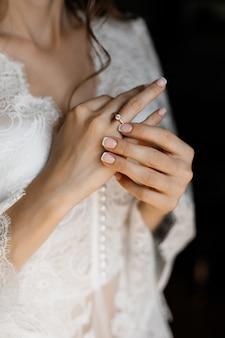 Mains d'une mariée avec une tendre bague de fiançailles sur
