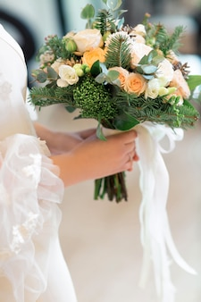Les mains de la mariée tiennent un magnifique bouquet de roses blanches. photographie d'art.